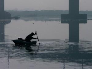 A man paddles across the Yamuna River