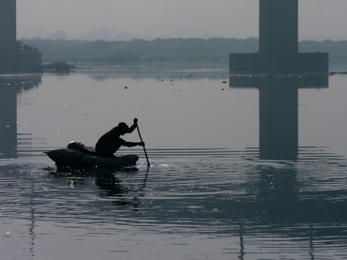 A man paddles across the Yamuna River