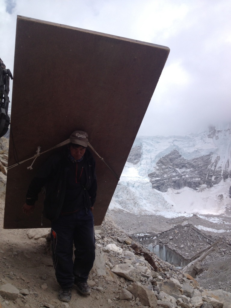 A Nepalese porter takes a wooden door up to the Everest base camp.