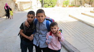 Three children wearing school backpacks in Tyre