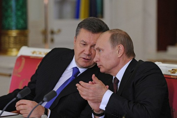 Ukrainian president Viktor Yanukovich and Russian president Vladimir Putin seated and talking in Kremlin
