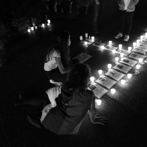 Protesters sitting alongside candles and photos of the dead