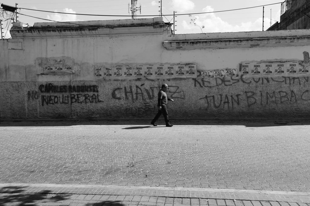 Man walking past graffiti-marked wall in Caracas