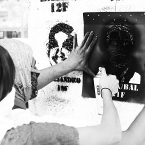Protester spray-painting a stencil of a dead protester's face on a wall
