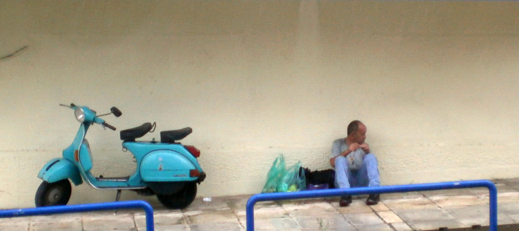 Homeless Polish immigrant sitting on the sidewalk next to a moped