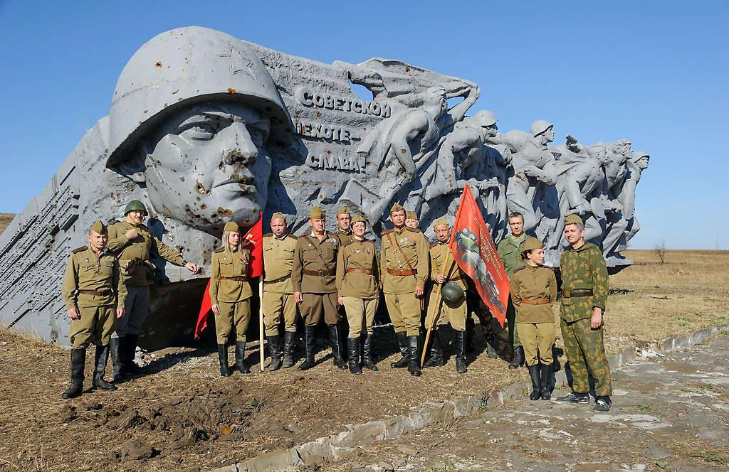 World War II reenactors pose in front of memorial
