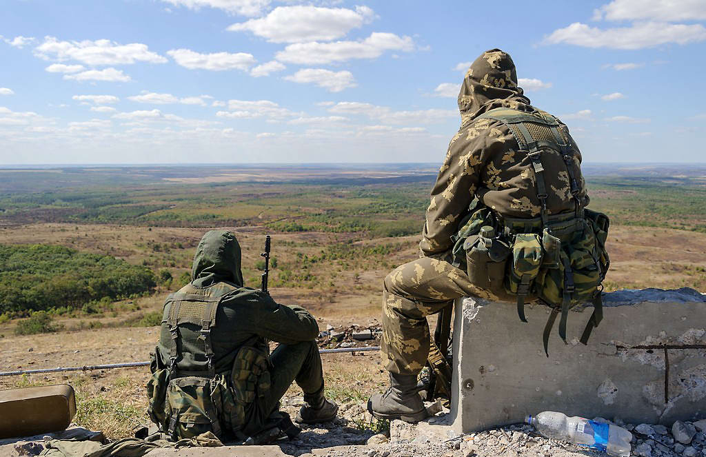 Separatist fighters sitting and looking out onto the steppe