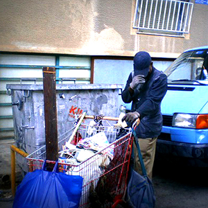 Ivorian immigrant Blaise pushes a shopping cart down the street while pulling down his cap to avoid identification