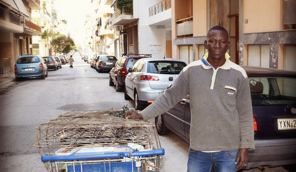 Nigerian immigrant Daniel Okator with a shopping cart full of scrap metal
