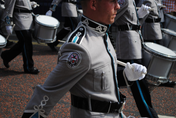 Gray-suited marching band walks by