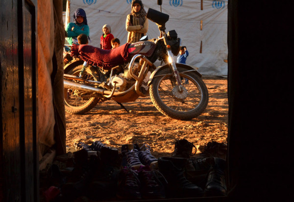 Women stand behind a motorcycle and in front of tents
