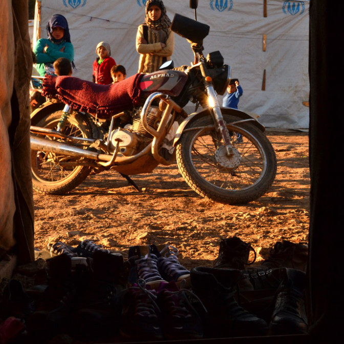 Women behind a motorcycle and in front of tents