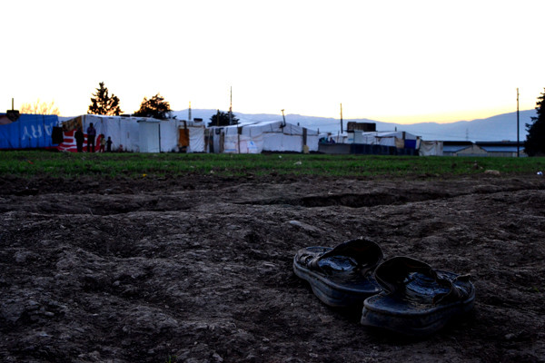 A pair of shoes in the foreground, tents in the background