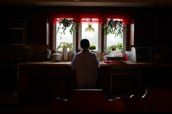 Myra, an undocumented Filipina immigrant, looks out the kitchen window of a friend's home on Staten Island
