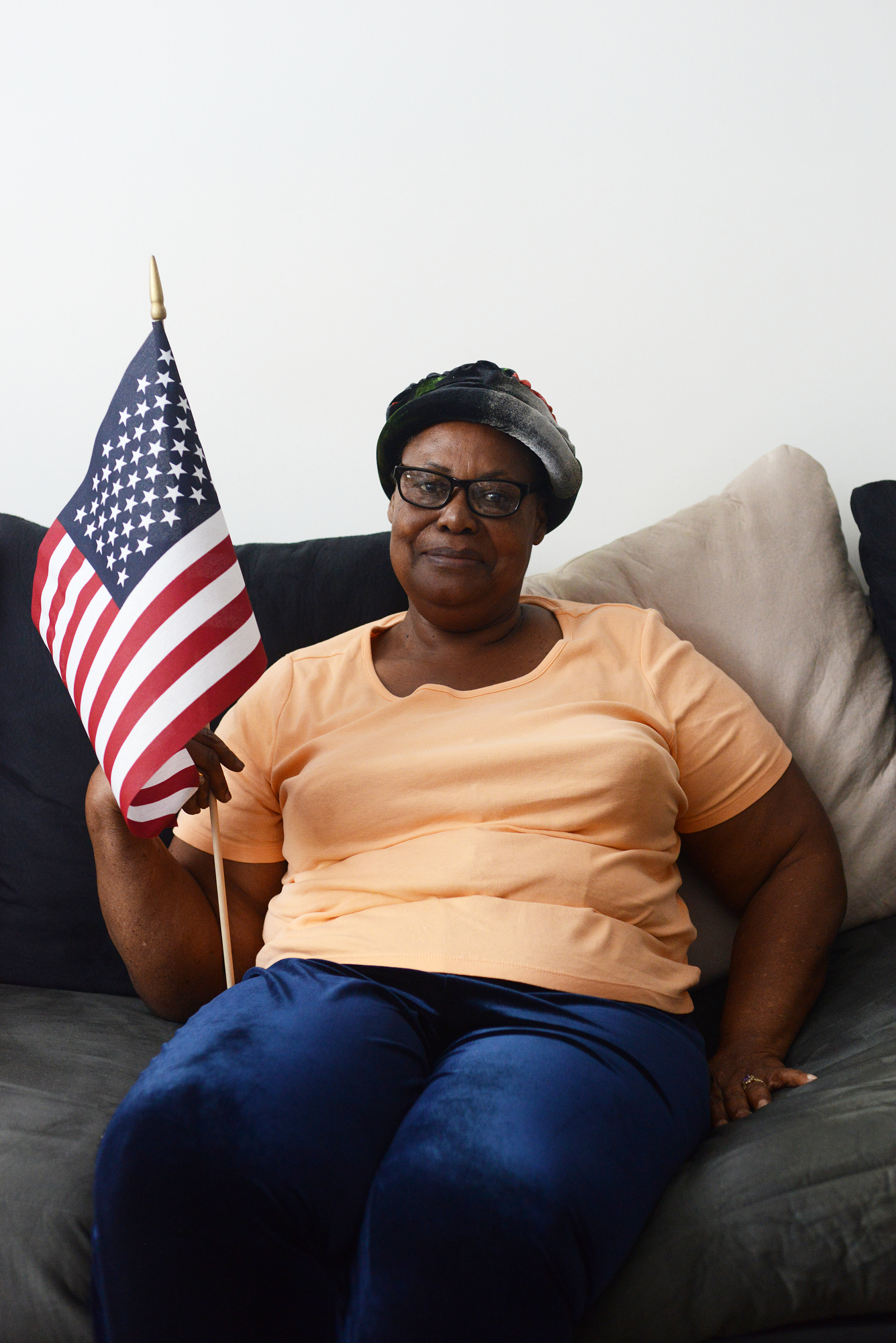Gloria Murray, an older Jamaican immigrant, holds a small US flag on the day she became a citizen
