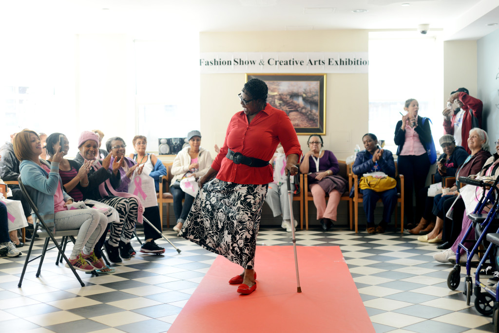 Gloria Murray, an older Jamaican immigrant, shows off her skirt on the runway of a fashion show at her senior housing project