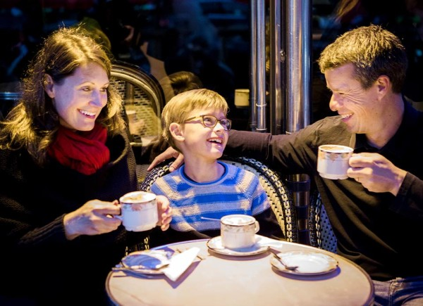 Parents laughing with their young son at a cafe