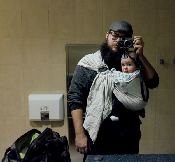 Father with baby in sling snapping photo in the mirror of a bathroom/changing room