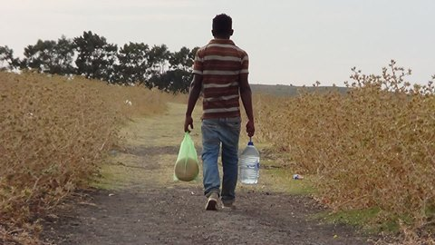 Man carrying plastic bag and water jug walking down dirt path