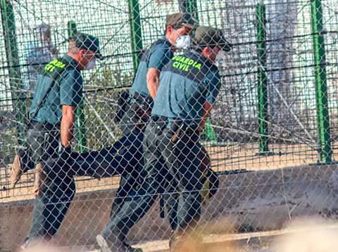 Three Spanish Civil Guard members carrying a man past the border fences