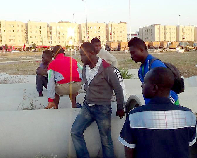 African men in Tangier sit among the concrete pipes they sleep in