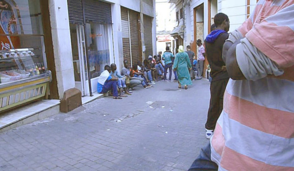 African immigrants squatting in the street in front of a Senegalese restaurant