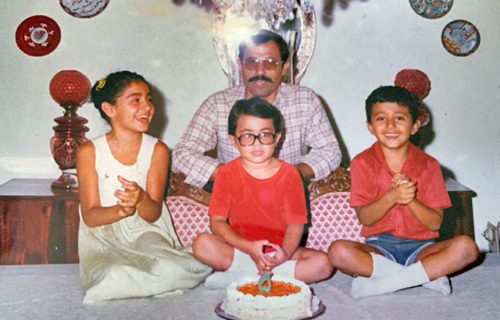 Bahar Anooshahr, her father, and her two brothers in front of a birthday cake