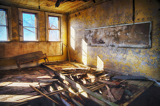 Decrepit classroom with blackboard in an abandoned school