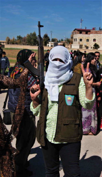 Women with headscarf holds an AK rifle
