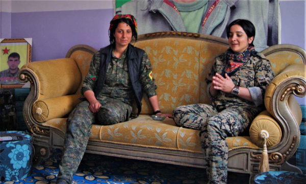 Two female YPJ soldiers sit on a couch